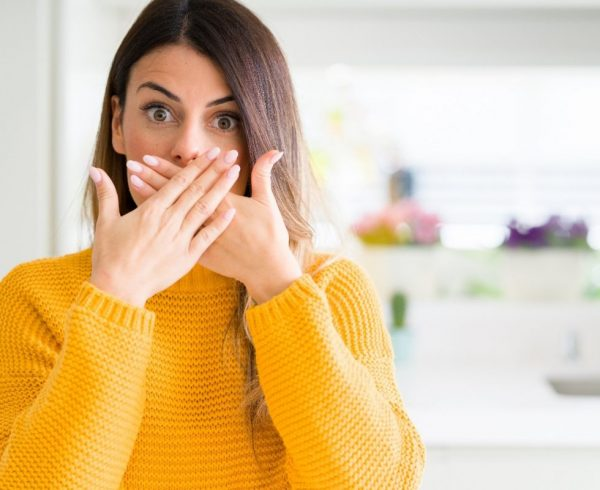 A woman facing the camera with a shocked face, her hands covering her mouth as if protecting her teeth.